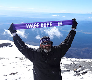 Joe Heiden stands atop Mount Adams in Oregon, at 12,280 feet, to Wage Hope two years after his pancreatic cancer diagnosis.