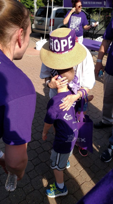 Six-year old son of father who lost his dad to the disease hugs a pancreatic cancer survivor at Cleveland walk/run event.