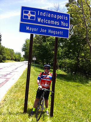 Cyclist Mike Blacconiere stands under Indianapolis welcome sign en route to PurpleStride, the walk to end pancreatic cancer
