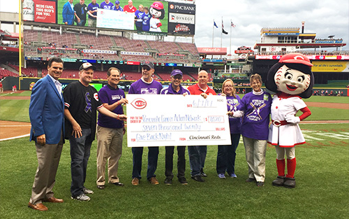 Cincinnati Affiliate volunteers stand on the Reds' Great American Ball Park field as they present a donation check for $7,020