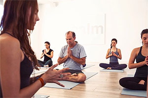 Young and mature students sit stress-free in Lauren Eckstrom's meditation class based on compassion