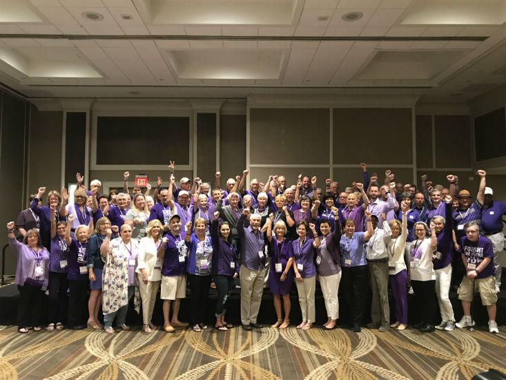 Advocates dressed in purple stand together cheering with their arms raised in our nation's capital.