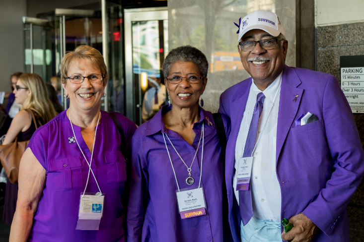 Three long-term survivors and PanCAN volunteers dressed in purple standing united together.