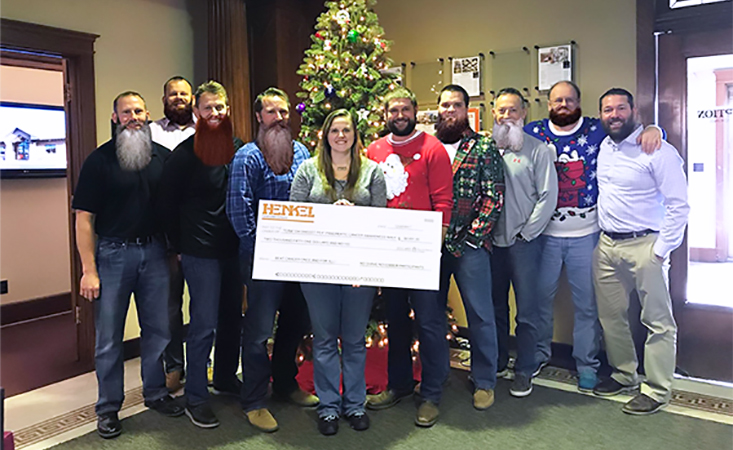 Fundraiser holds big novelty check with coworkers in support of fighting pancreatic cancer