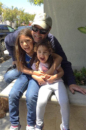 Pancreatic cancer survivor and father laughing with his two young daughters