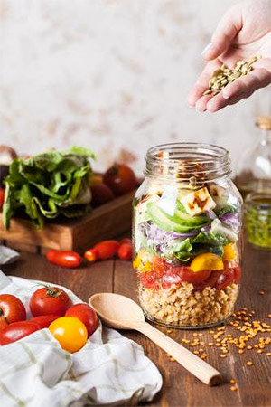 A mason jar filled with ingredients to make a salad, including fresh grains and produce.